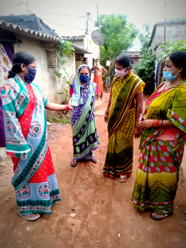 Group of women dressed in Indian saris standing in a circle outdoors with their mouths covered