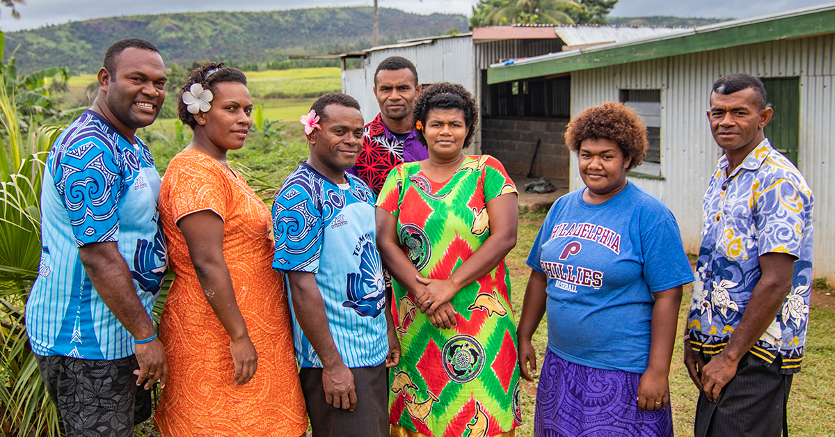 A youth group dressed in colourful floral clothing stand smiling at the camera in a village, there are a mix of men and women