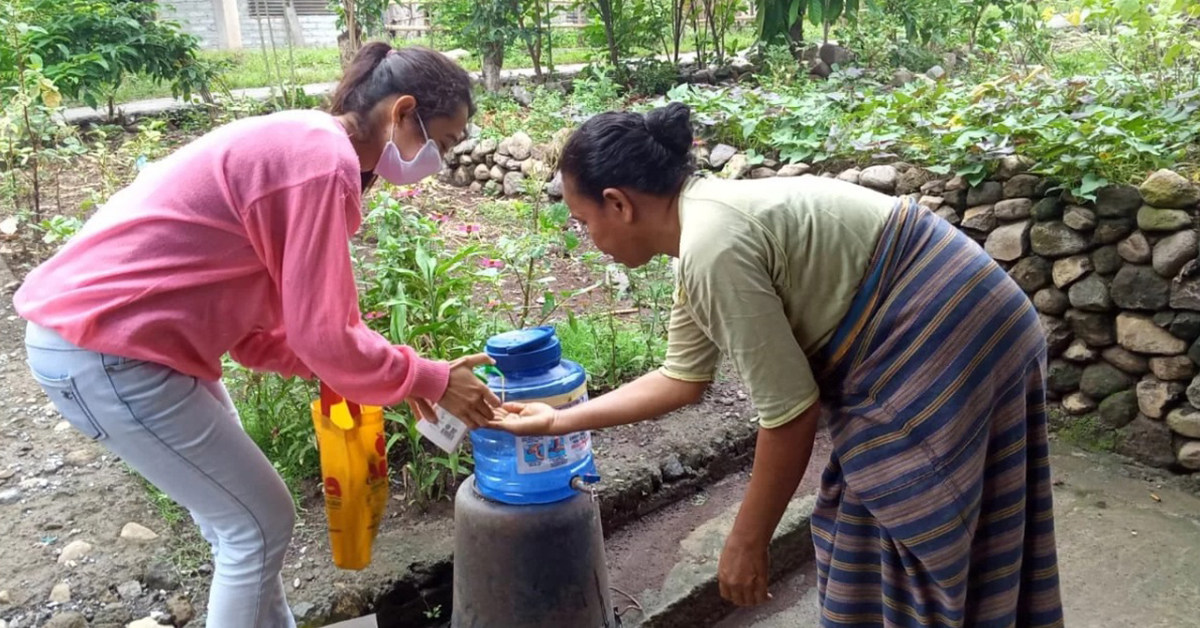 One woman in a mask is helping another woman use a portable handwashing station set up outdoors