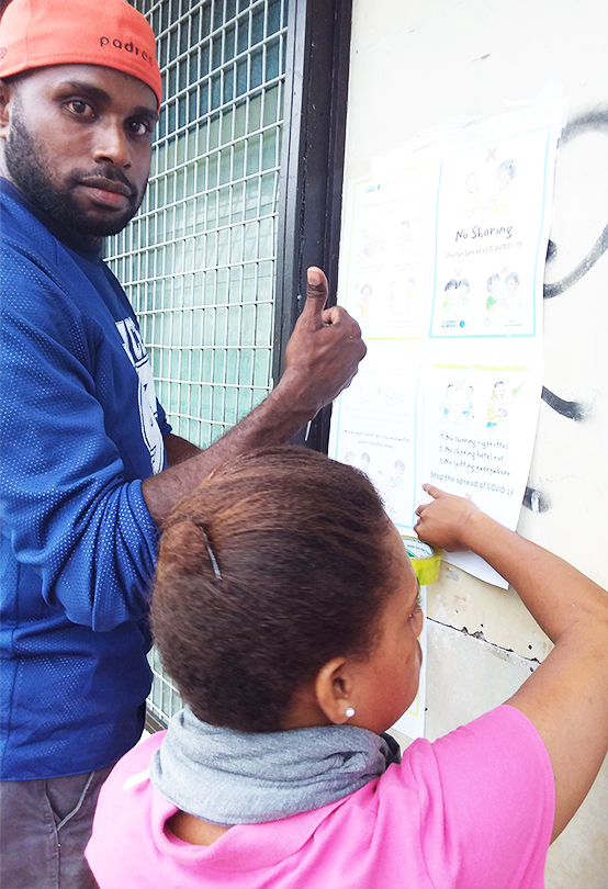 Man and woman are putting up COVID-19 prevention posters in public in Papua New Guinea, the man shows a thumbs up to the camera as they work
