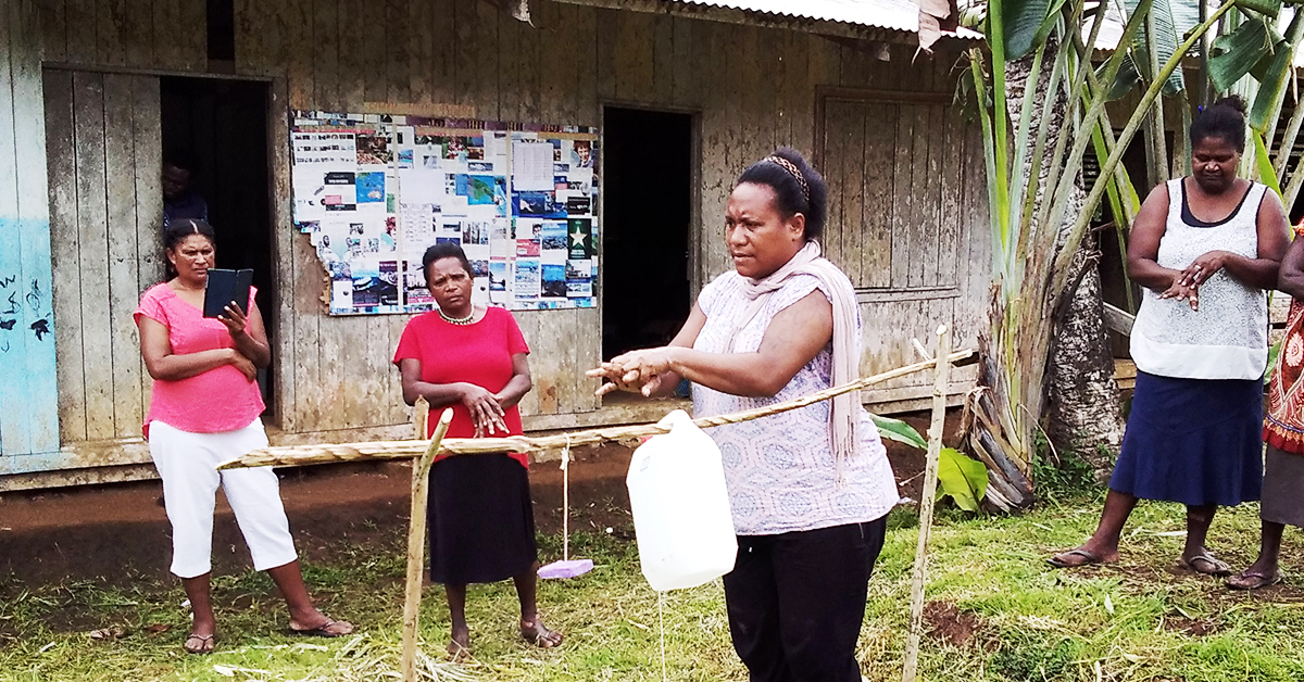 A woman in PNG is demonstrating how to wash your hands properly using a tippy tap device and people watch on