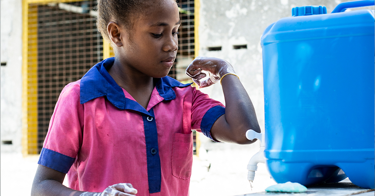 Young school girl washes her hands carefully at a handwashing station at school