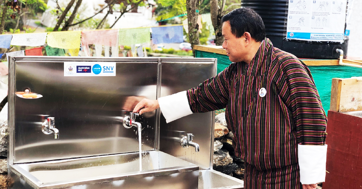 A man turns on a tap at a newly installed metal public handwashing station