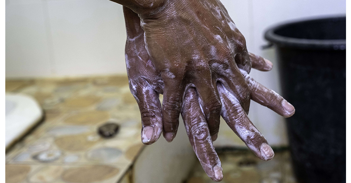A close up pair of hands covered with soap while handwashing - Proper handwashing with soap is a critical line of defence against COVID-19