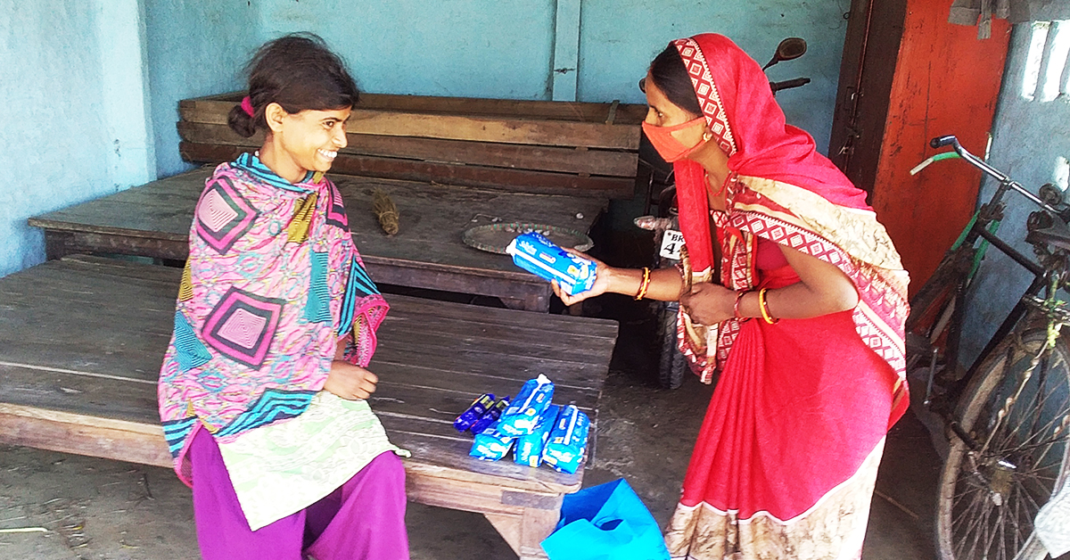 A woman is handing sanitary pads to a disabled woman