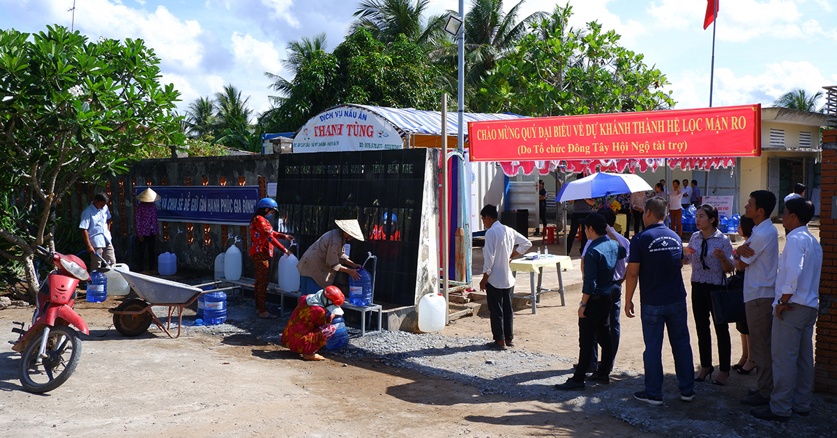 Groups of Vietnamese people getting water from a water kiosk in a public place outdoors