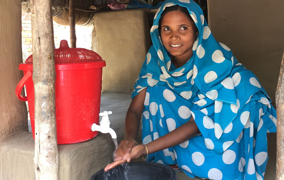 A young woman crouches by a red handwashing device to wash her hands, she is smiling