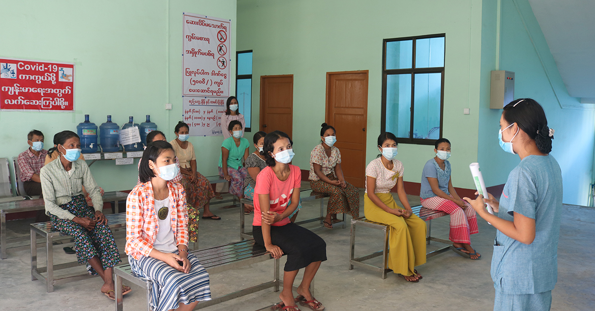 A room full of women in a healthcare facility receiving training, all are sitting 1.5m apart and wearing face masks, in line with COVID-19 prevention measures