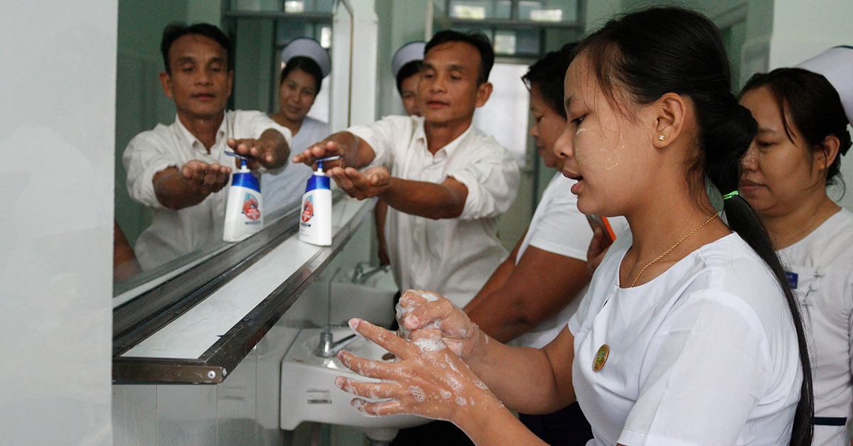 Group of hospital workers washing their hands at a long steel handwashing station