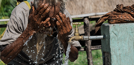 Elderly vision impaired man washes his face with clean water running from a tap