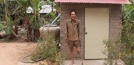 Happy man stands in front of his accessible latrine