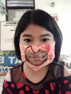A young girl models an innovative accessible face mask with a clear window so those deaf and hard of hearing can still lip read