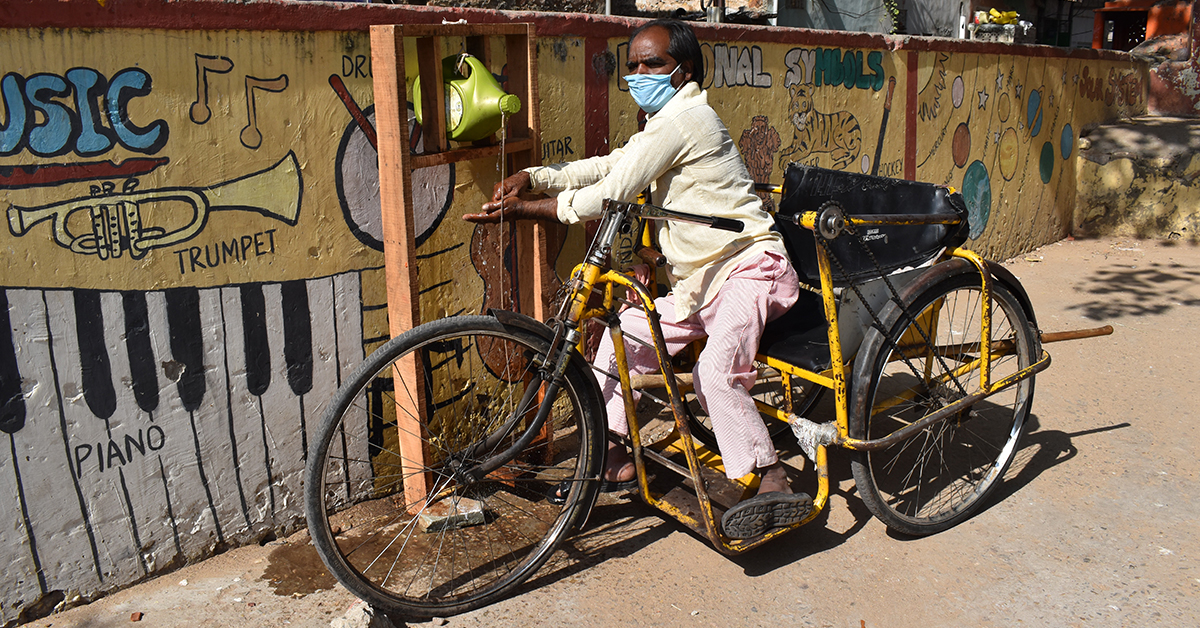 A man on a large yellow wheelchair trike is washing his hands at a handwashing station next to a wall with brightly coloured street art