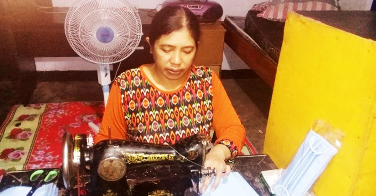 a woman is sitting at an old fashioned sewing machine sewing a mask