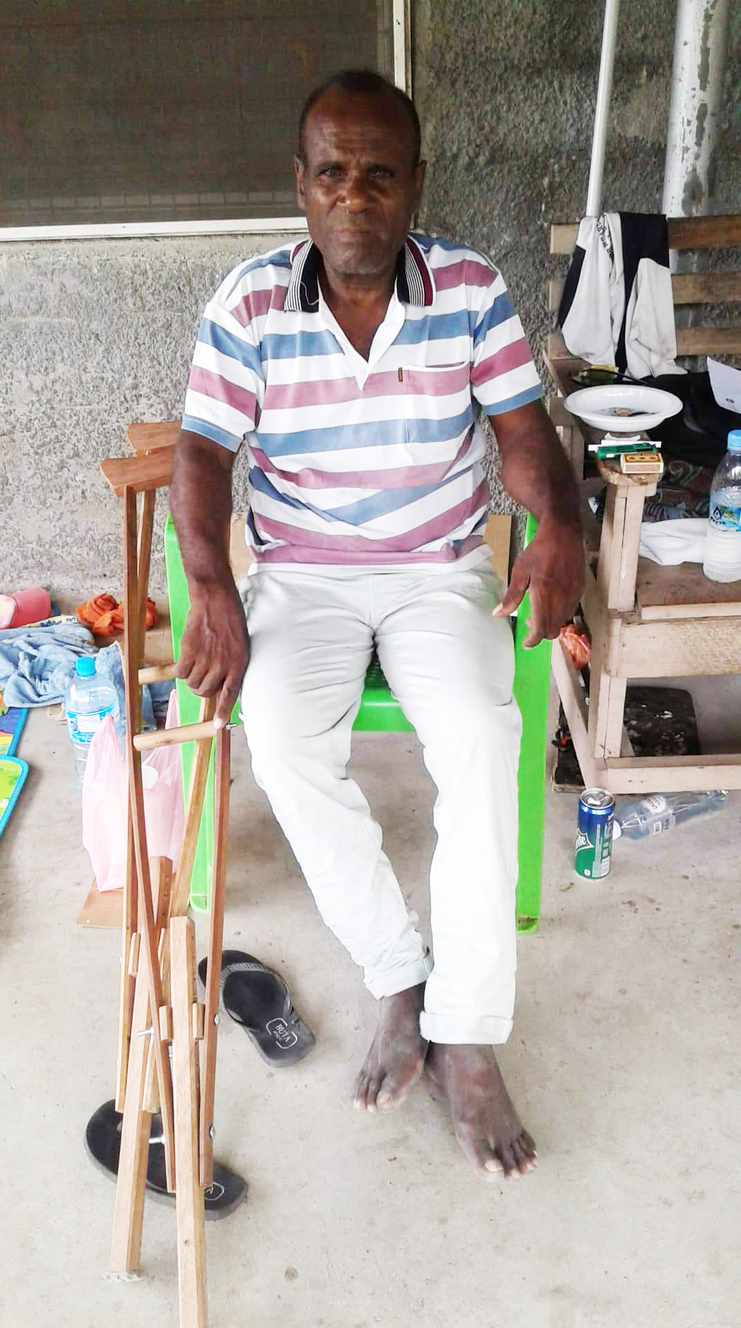 Man with a disability sits in his home in Solomon Islands