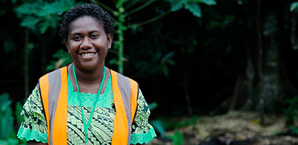 Woman smiles at camera wearing a hi vis vest