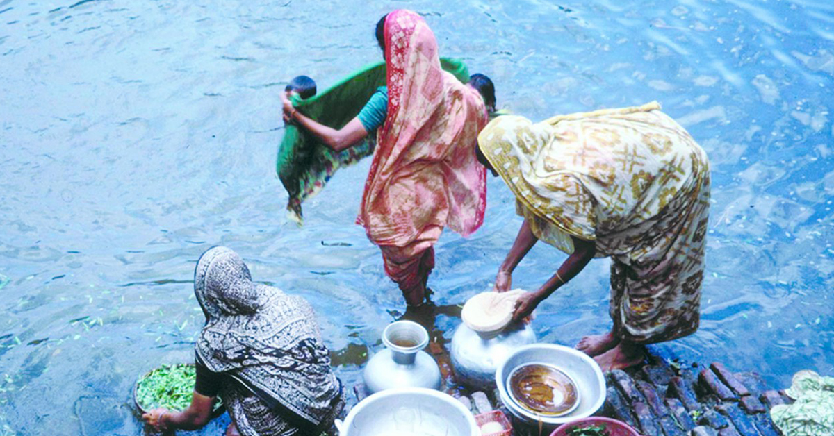 Three women in Bangladesh hand wash their clothes, dishes and food at the waters edge, their backs are facing the camera and one is crouching, the others are standing at different stages in the process