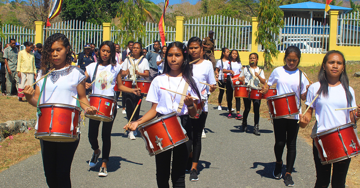 Group of young women marching and playing red drums in celebration