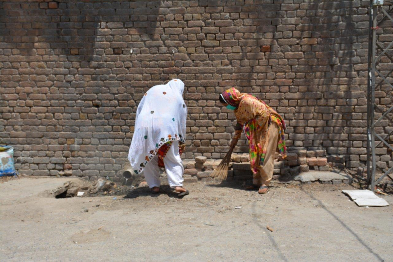 two women are cleaning up an area outside to improve the sanitation of their village