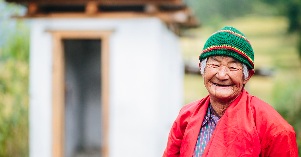 Elderly woman is smiling standing in front of a newly constructed toilet