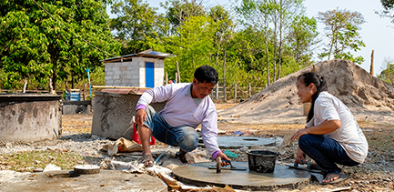 A smiling man and woman squat down constructing toilet materials on a sunny day