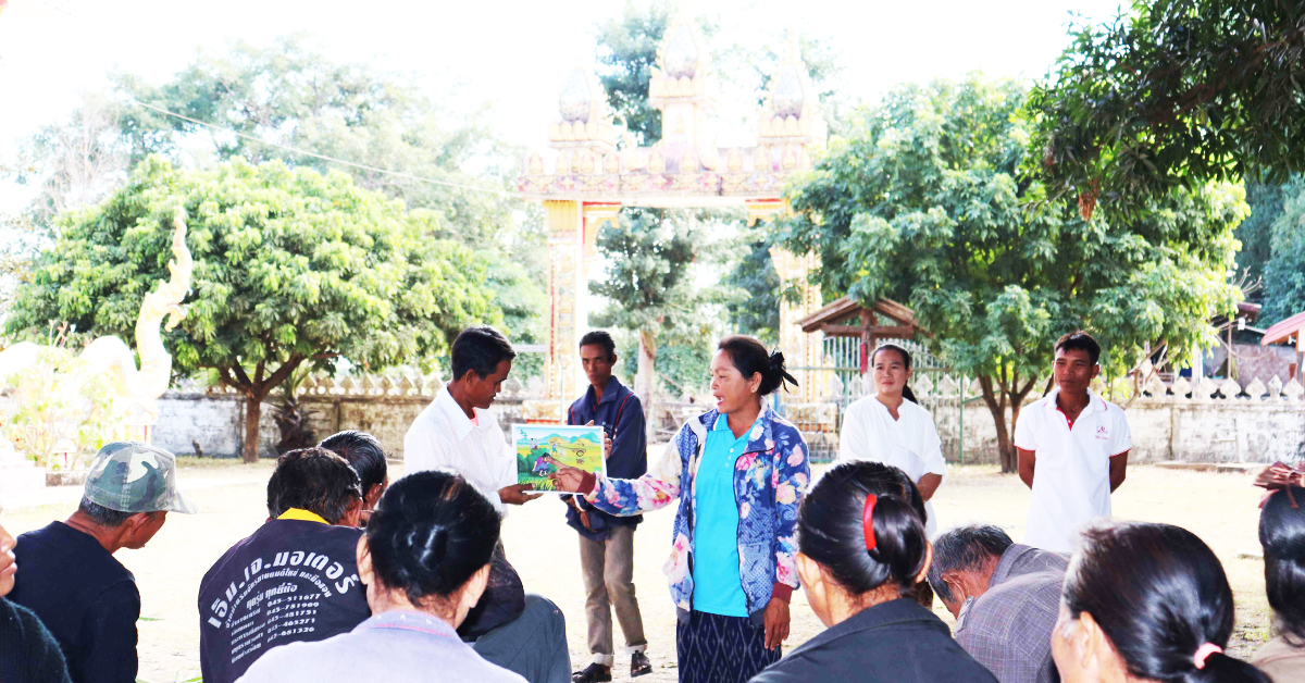 Woman sanitation promoter is holding a visual in front of a group of people outside in a rural village