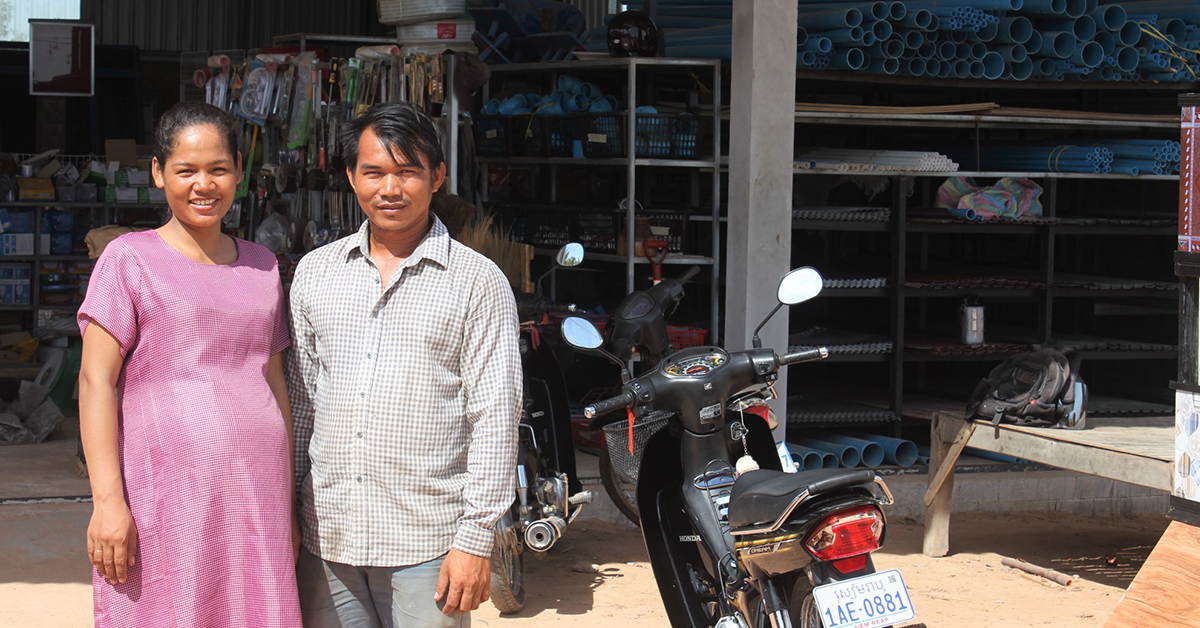 A couple stand smiling outside of their newly built sanitation supply business