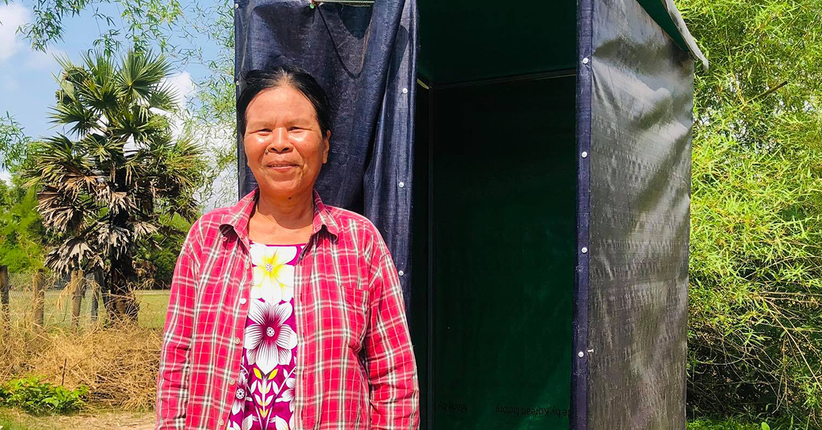 A woman stands smiling in front of her newly constructed latrine in Cambodia