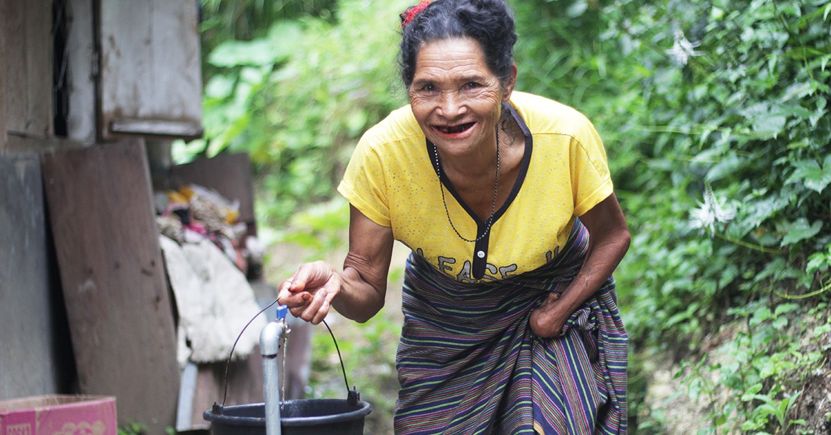 Elderly woman smiles at camera while she collects water with a bucket