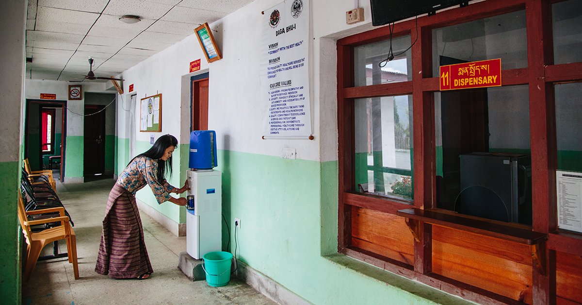 A woman accesses drinking water for patients and visitors in a health care facility in Bhutan