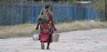 Woman walking along a dirt road carrying water buckets