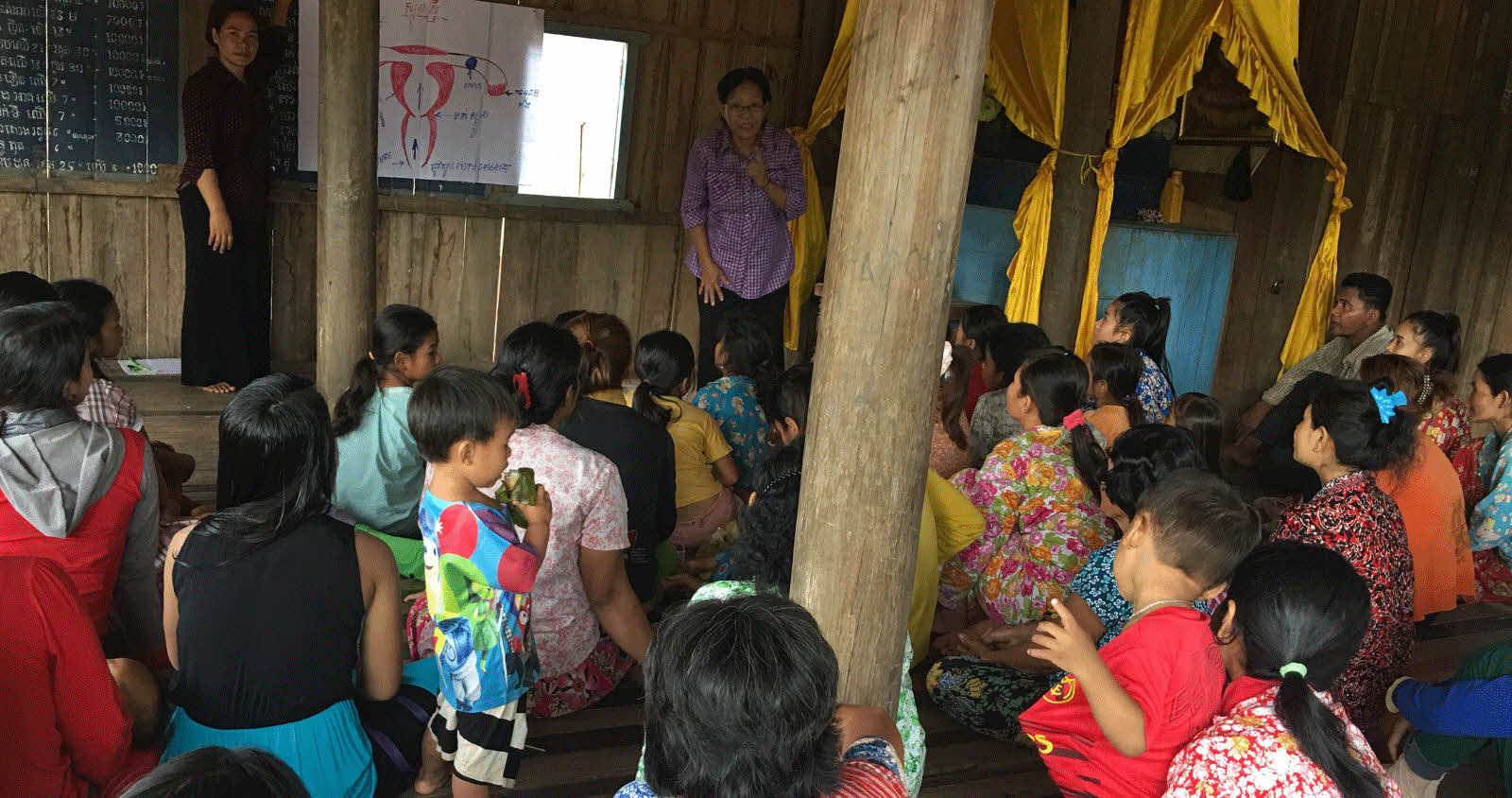 women speaking to a group of children