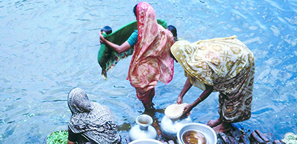 three women are at the water's edge washing clothes, food and dishes in Bangladesh